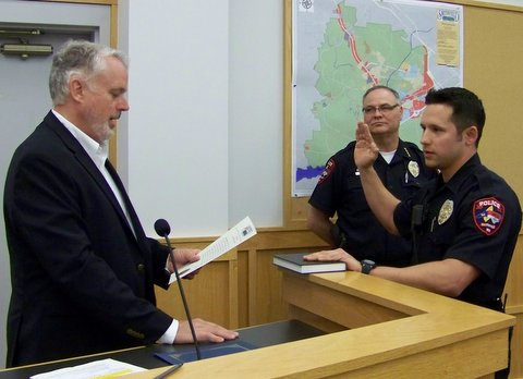 Officer Gabriel Galindo is sworn in by Smithfield Mayor John Lampe as Police Chief Michael Scott looks on. WTSB Photo