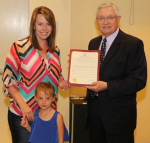 Caption: Mayor Pro Tem Michael Grannis presents Payton and Molly Herring with Promise Walk proclamation
