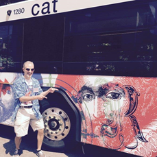 West Johnston High Art Teacher Frank Kreacic stands behind the Raleigh bus which features his art.
