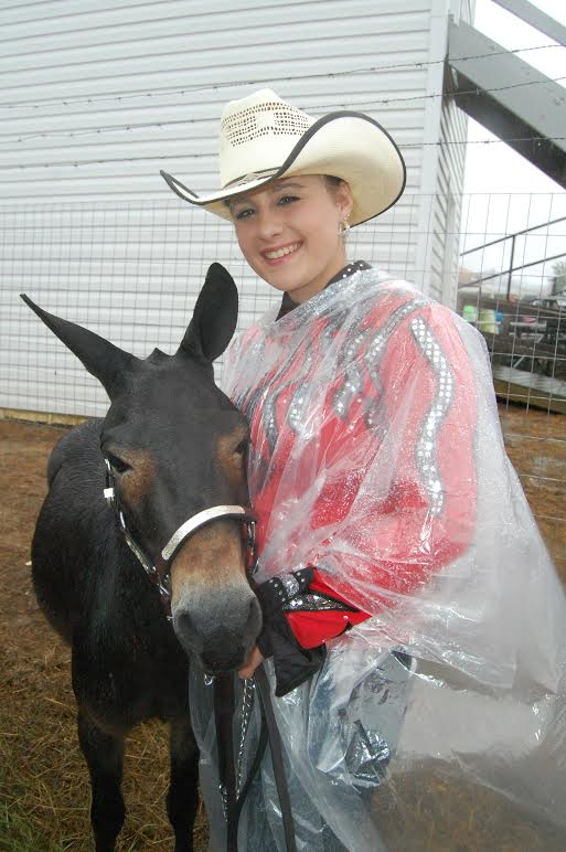 The 66th annual Mule Days celebration saw some wet weather during the weekend. There were just as many rain slickers as cowboy hats, but the festivities stubbornly continued on. In the photo, Lizzy Scott, 18, of Benson, poses with her miniature mule Snickers outside the Nowell Smith Arena in Benson's Chamber Park on Friday morning before the mule judging competition. Courtesy The Daily Record