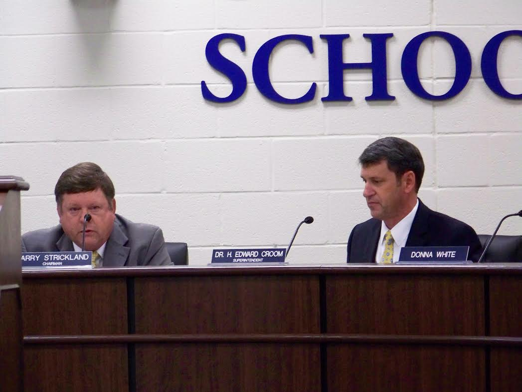 School Superintendent Dr. Ed Croom (right) listens as Board Chairman Larry Strickland reacts to the news Dr. Croom will be retiring from Johnston County Schools on March 1, 2016. WTSB Photo