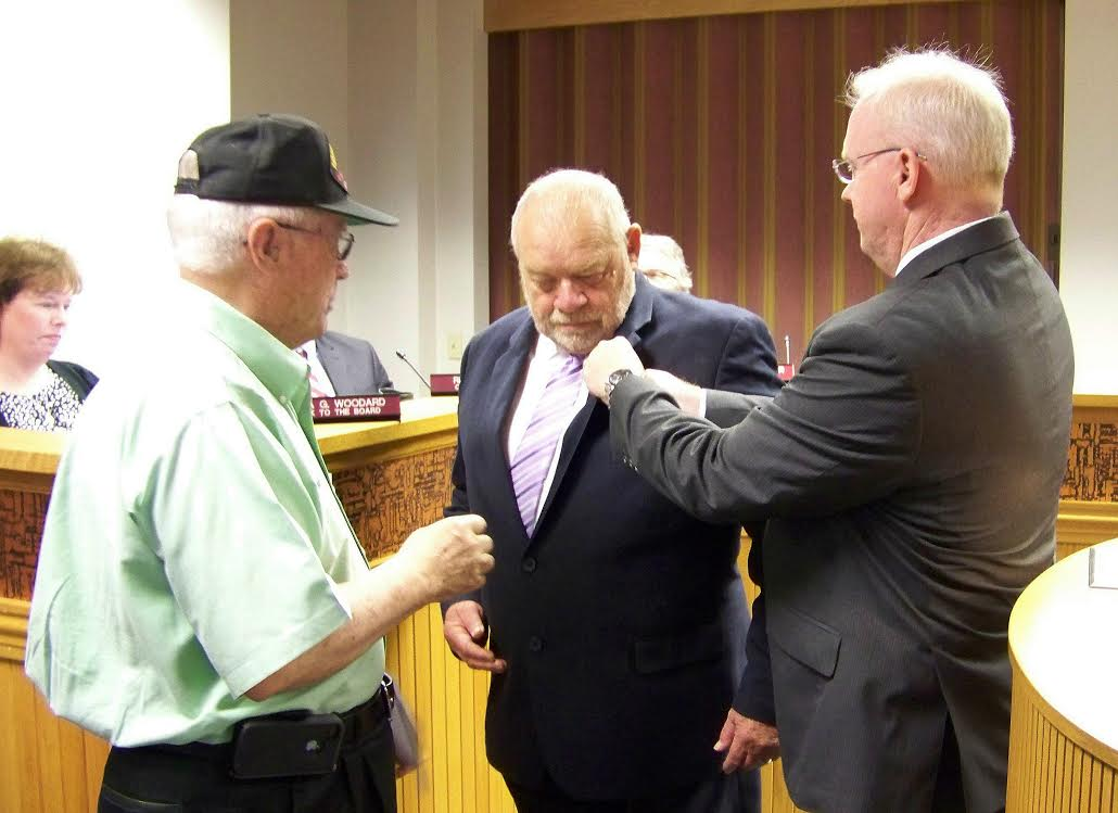 Johnston County Commissioner Chairman Tony Braswell (center) receives his Vietnam Veteran's Lapel Pin during a surprise presentation from Colonel Rudy Baker (left) and Veterans Administration Director Robert Boyette (right). JoCoReport.com Photo