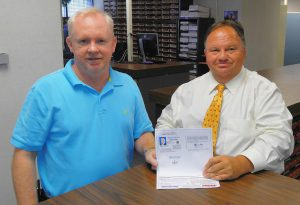 "(Left to right) Johnston County Veterans Services Director Robert Boyette and Johnston County Register of Deeds Craig Olive display a ""Thank a Vet"" Photo ID card that is being distributed to area veterans to receive discounts at participating businesses. The discount program will launch November 1st."