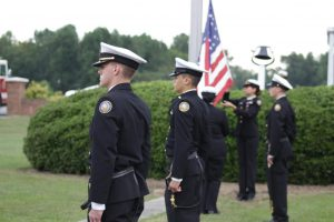 NJROTC Cadets Joseph Murdoch (left) and Isrrael Borbonio (right) participate in the September 11th commemoration ceremony as their fellow cadets raise the American flag.