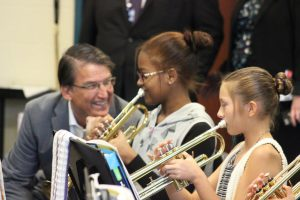 NC Governor Pat McCrory (left) listens to Riverwood Middle students (from left) Yena Brown and Alexandria Watson play the trumpet.